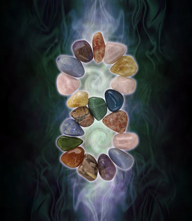 Infinity Crystals and spiralling energy - black background with a double spiral energy field behind a crystal infinity formation comprised of tumbled healing stones
