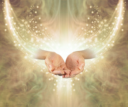 Golden Healing Resonance  - female cupped hands emerging from arc of shimmering sparkles on a glowing golden ethereal energy formation background with copy space Reklamní fotografie - 114467944