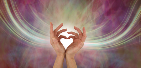 Sending out love vibrations - female hands making a heart shape with a stream of energy flowing either side on a warm multicoloured ethereal background and copy space Stock Photo