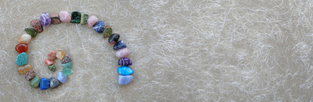 Crystal Fibonacci Spiral Background Banner -  carefully arranged crystal healing gemstones in spiral shape on left against rustic buff coloured fibre paper with copy space on right