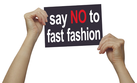 Say NO to fast fashion campaign sign - female holding up a placard with red and white text on a black card isolated against white