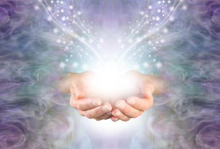 Het verzenden van helende energie met hoge resonantie - vrouwelijke tot een kom gevormde handen die tevoorschijn komen uit een lila blauwe wervelende energieveldachtergrond met glinsterende sprankeling wit licht en kopieerruimte