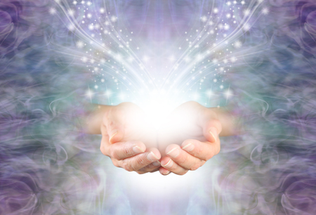 Sending High Resonance Healing Energy - female cupped hands emerging from a lilac blue swirling energy field background with shimmering sparkles white light and copy space