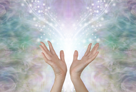 Energy flows where your attention goes - female hands reaching up towards a symmetrical shower of glittering sparkles against an ethereal pale green gold energy background Stock Photo