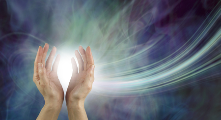 Stunning Healing Energy phenomenon - pair of hands reaching up into a ball of white energy with a laser trail and green blue purple ethereal energy field background
