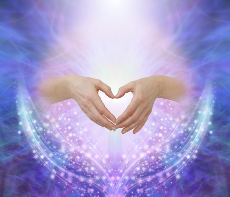 Healers hands making a humble heart shape - female hands forming a heart shape against a pink circle surrounded by ethereal blue and beautiful glittering sparkles with copy space above Stok Fotoğraf