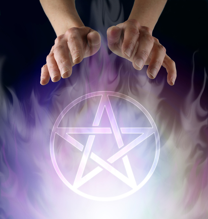 Wiccan Pentacle Ceremony - witchs hands hovering above a transparent Pentacle symbol floating in smokey ethereal atmosphere  against a black background with copy space
