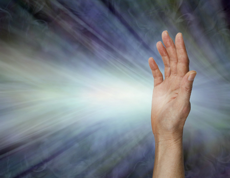 Female Pranic healer sending focused energy from right hand palm chakra - upright open hand facing out with a stream of white energy flowing horizontally against a blue energy field background with copy space