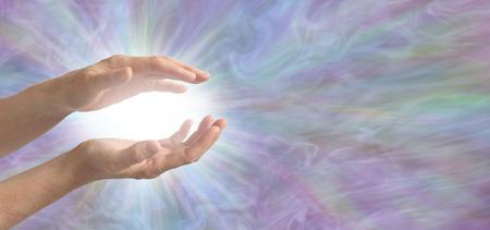 Démonstration d'une harmonisation avec une énergie de guérison phénoménale - des mains féminines en coupe autour d'une lumière vive sur un fond de formation d'énergie multicolore fluide avec un espace de copie pour les messages Banque d'images