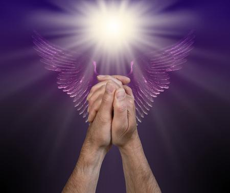 Orando por ayuda de los Reinos Angélicos: manos masculinas en posición de oración con una luz blanca brillante arriba y un par de alas de ángel púrpura