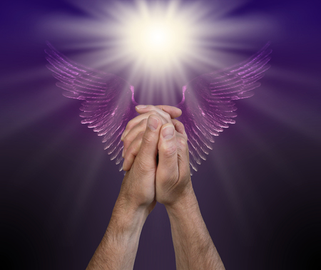 Praying for help from the Angelic Realms - male hands in praying position with a bright white light above and a pair of purple Angel wings