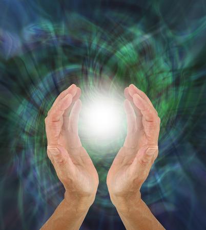 Orb Light Paranormal Phenomenum - mains en coupe autour d'une lumière blanche brillante sur fond de champ d'énergie rotatif vert avec espace de copie