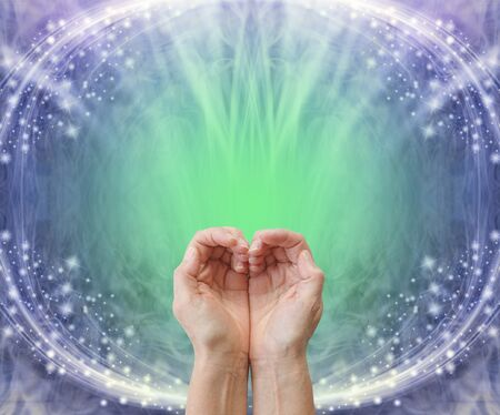 Sending heart chakra healing energy background - pair of cupped hands making a heart shape against a blue and green back ground with copy space and white sparkles creating an oval frame Imagens