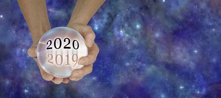2019 to 2020 Crystal Ball Predictions Banner - female hands holding a large crystal ball with the years 2019 and 2020 against a Cosmos dark blue starry night sky  background with copy space