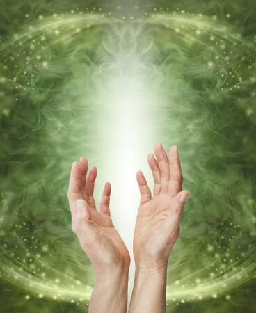 Sending Heart Chakra Healing Energy - female hands reaching up sending energy against a shaft of white light a green ethereal energy flowing sparkling background with copy space