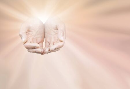 Thanksgiving Offering Message Board - male cupped hands merging with bright white star burst on peach flesh coloured background with space for copy Imagens