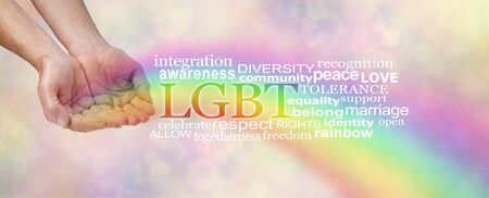 LGBT awareness word tag cloud - male hands in open cupped position with a rainbow flowing outwards and an LGBT word cloud  beside on a soft peach bokeh background