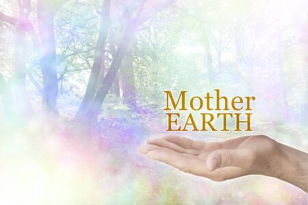 Be kind and loving towards Mother Earth - male open palm with the words MOTHER EARTH floating above on a rainbow coloured tree landscape bokeh background with copy space