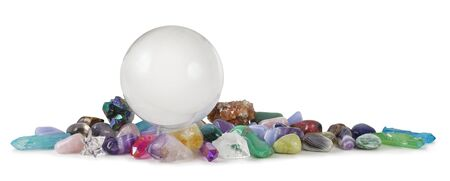 Multicoloured Healing Crystals Background Banner - Huge Clear Crystal Ball surrounded by various tumbled healing stones and terminated quartz with space for copy