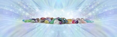 The Mystical Energy of Earths Crystals - wide row of different coloured healing stones and terminated quartz against radiating sparkling blue energy flowing outwards with copy space