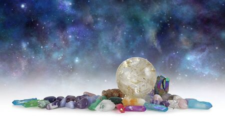 Cosmic Space Crystals Background Banner - Huge rutilated Crystal Ball surrounded by tumbled healing stones and terminated quartz with space for copy above in celestial dark night sky