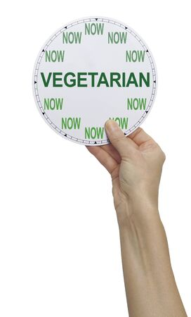 Its time to become a Vegetarian NOW - female holding up a clock where NOW replaces the numbers and across the middle is written VEGETARIAN, isolated on a white background Banco de Imagens
