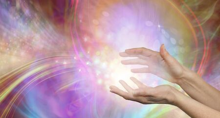 Sending you beautiful healing energy vibes - female cupped hands with white energy formation flowing outwards, sparkles and colours moving in all directions with copy space Banque d'images