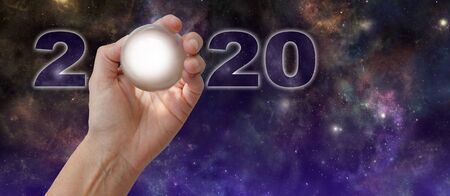Crystal Ball Reading - What does 2020 hold for you - female hand holding a clear crystal ball making the 0 of 2020 against a dark night sky deep space background with copy space