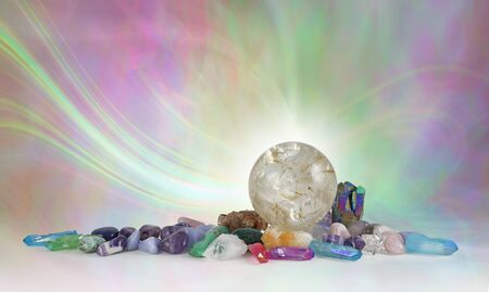 Rutilated Quartz Crystal Sphere Background - beautiful massive quartz ball surrounded by assorted tumbled healing stones against an ethereal pink green energy formation background with copy space
