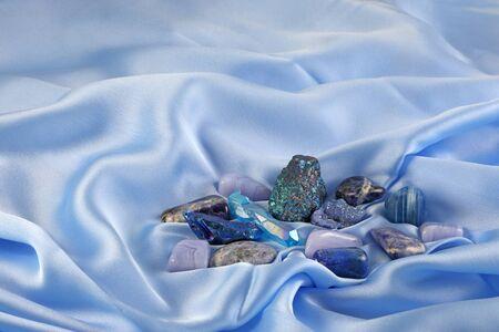 Cristaux de guérison du chakra de la gorge bleue sur soie bleu clair - assortiment de minéraux de quartz de cristal de couleur bleue posés sur un tissu de soie fine bleu avec espace de copie au-dessus