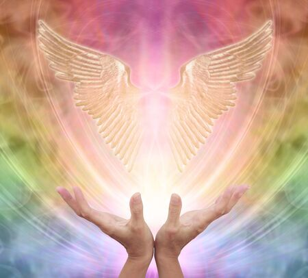 Seeking help and guidance from your Guardian Angel - female hands reaching up towards a pair of gleaming shimmering angel wings against an ethereal rainbow coloured energy background