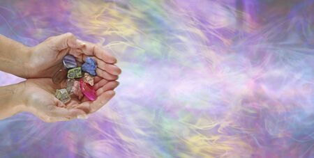 Crystal healing practitioner message banner -  female crystal therapist with cupped hands containing a selection of tumbled stones against an ethereal multicoloured flowing energy  background