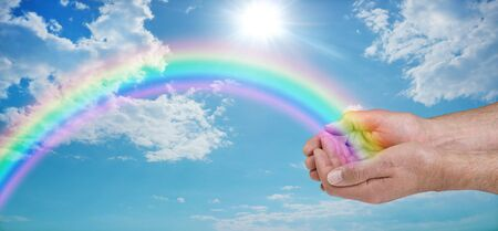 Sending you beautiful rainbow healing energy - male cupped hands with a vivid rainbow arcing outwards against a blue sky, with clouds and a sun burst with copy space