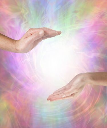 Combining our yin and yang energy creates pure healing - male hand opposite female hand with a white light orb in between against a multicoloured flowing energy field background with copy space