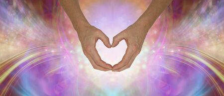 Sending you pure unconditional love - hands making a gentle heart shape against an ethereal shimmering multicoloured energy field background with copy space