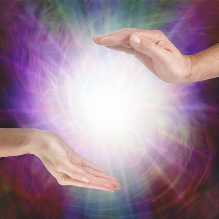 Together our healing energies combine to create a powerful influence - male hand opposite female hand with a white light orb in between against a multicoloured flowing energy field background with copy space Standard-Bild