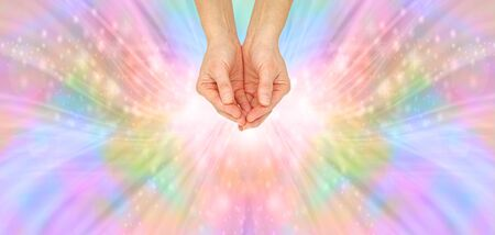 Focusing and Sending Beautiful Rainbow Healing Energy - female with cupped hands against a multicoloured outward flowing energy formation background with copy space