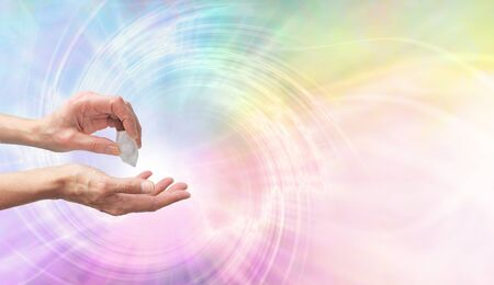 Crystal Healer using clear quartz terminate wand - Female hand pointing a clear quartz terminated crystal into palm of hand against a rainbow coloured spiraling  vortex background with copy space on right