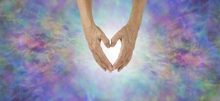 Love Heals Everything Concept Banner - female hands making a heart shape with white light behind and beautiful multicoloured energy field either side with copy space Фото со стока