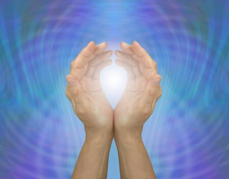 Pulsating Quantum Healing Energy  - cupped female hands embracing white healing light against a blue green energy matrix background