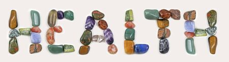 Tumble stone healing crystals spelling out HEALTH - random different coloured healing stones formed to make the word HEALTH isolated against a white background