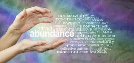 Attract Abundance Word Tag Cloud - female hands with the word ABUNDANCE floating between surrounded by a relevant word cloud on a rainbow coloured  rustic grunge background Archivio Fotografico