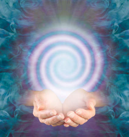 Observe the continuous vortexing spiral of energy flowing in and out - female cupped hands with a pink spiral above against an intricate jade green purple energy background and copy space