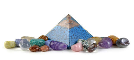 Orgone pyramid power and healing crystals - copper spiral and clear quartz on top of blue chip stones inside Orgone pyramid surrounded by mixed tumbled healing stones isolated on white background