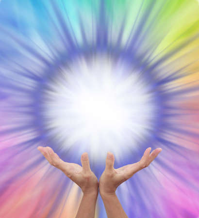Extraordinary Multicoloured Energy Field Formation - female cupped hands reaching up to a bright white orb surrounded by rainbow colours radiating outwards with copy space Stock fotó