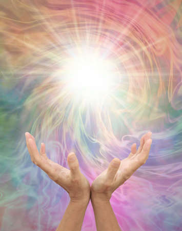 Connecting to Higher Dimensional Power for Inspiration - female open hands reaching up to a bright white light against a multicoloured vortex energy field with copy space Stock fotó