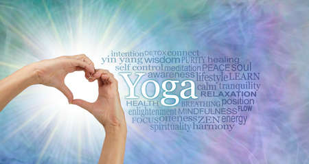 Words associated with the benefits of YOGA - female hands making a heart shape with light burst behind beside yoga word cloud on a blue green purple gaseous background Standard-Bild