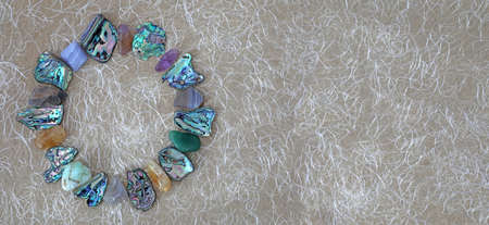 Crystal and Abalone Shell Circle Website Header - tumbled stones and slices of abalone shell neatly arranged in a circle border against handmade fibrous beige paper with copy space on right