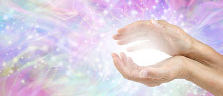 Sensing Awesome Metaphysical Energy Field between hands - female cupped hands with white healing energy against a colourful blue purple green sparkling chaotic background with copy space Stock Photo