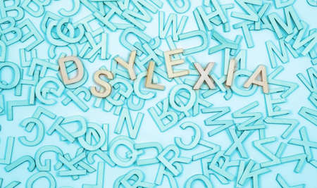 Wrongly spelt Dyslexic word concept background - jumbled alphabet letters in turquoise blue with the word dyslexia spelt wrong on top and space for message